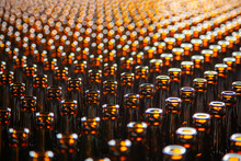 Glass Bottle Texture. Glass Bottle At Factory For Production Of Glass Containers. Many Of Transparent Brown Glass Bottle Into Row, Close Up.