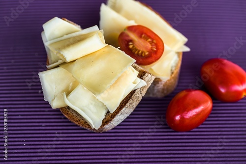 Bread with sliced cheese and tomato on violet background.