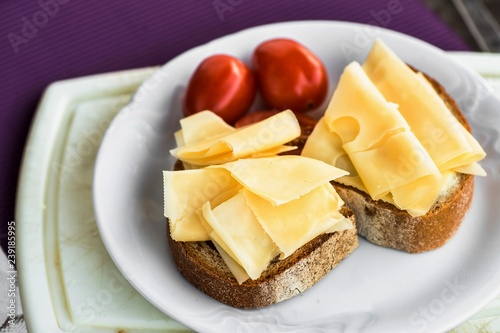 Snack with sliced cheese, bread and tomato.
