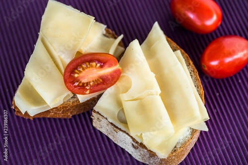Two breads with sliced emmental and tomato, violet background.