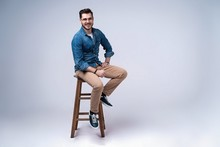 Full Length Portrait Of An Attractive Young Man In Jeans Shirt Sitting On The Chair Over Grey Background.
