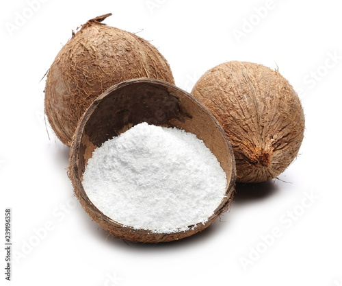 Pile of shredded coconut meat in half shell isolated on white background