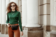 Outdoor Fashion Portrait Of Young Lady Wearing Sunglasses, Green Turtleneck, Brown Trousers, Leather Belt Bag, Necklace, Bracelet, Posing In Street Of European City. Copy, Empty Space For Text