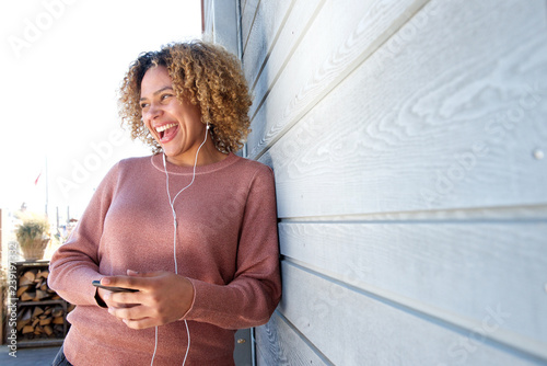 happy woman enjoying music with earphones and mobile phone - 239197332