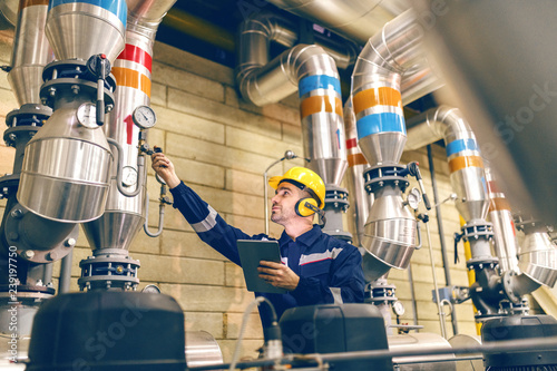 Young Caucasian worker in protective suit tightening the valve and using tablet while standing in heating plant Fototapeta