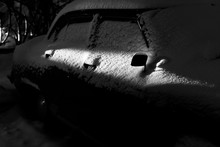 Snow Covered Old Classic Car Illuminated By A Ray Of Light At Night. Old Car Covered With Snow. Soviet Car Volga. Details Of A Car Covered With Snow