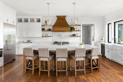Obraz Beautiful Kitchen Interior in New Luxury Home with Large Island, Hardwood Floors, and White Cabinets and Countertops - fototapety do salonu