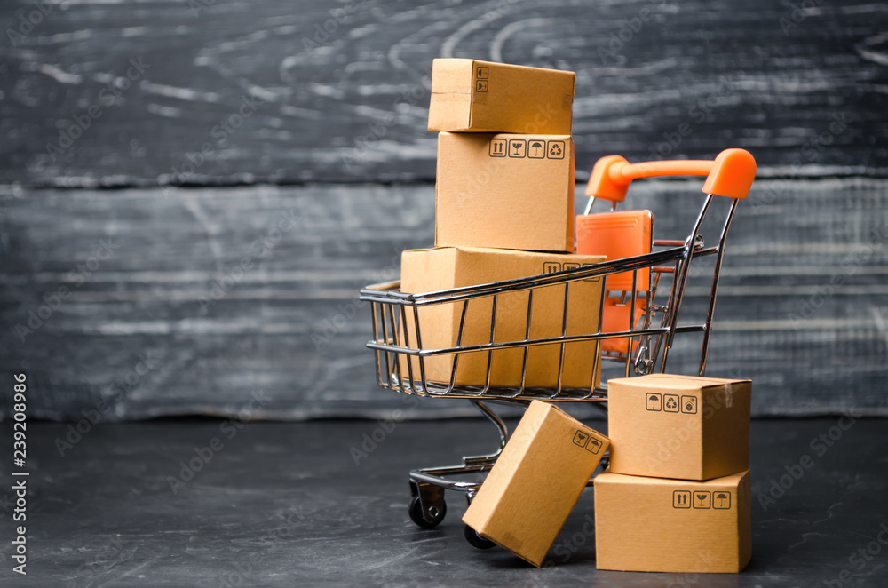 Fototapeta A supermarket cart loaded with cardboard boxes. Sales of goods. concept of trade and commerce, online shopping. high. delivery order. purchasing power of the population and the state of the economy