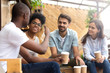 canvas print picture - African American man showing thumb up, telling story to interested attentive friends, sitting, drinking coffee in cafe together, smiling multiethnic friends discussing, talking, chatting