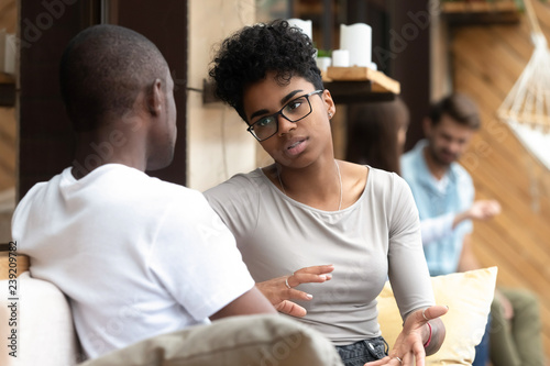 Photo Focused African American woman talking with man in cafe, girlfriend discussing r