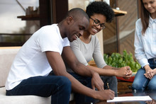 Happy African American Couple Signing Contract, Making Agreement With Businesswoman, Female Realtor, Wedding Planner, Financial Advisor, Smiling Clients With Seller In Cafe, Successful Negotiations