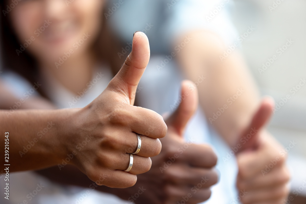 Fototapeta Happy multiethnic friends showing thumbs up close up, like, finger, gesture, recommendation of good choice, excited satisfied clients, successful teamwork, hands view, celebrate great deal