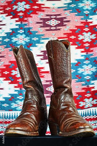 Valokuva  Vintage Caribou Hide Cowboy Boots against Colorful Indian Blanket