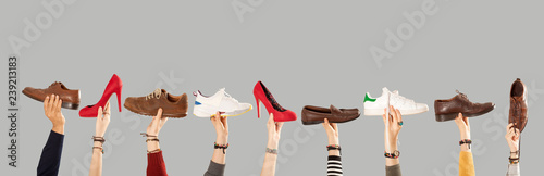 arms raised and holding shoes