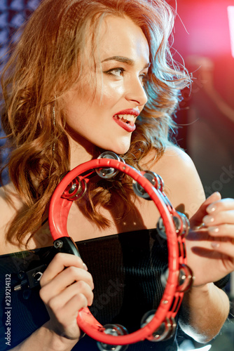 Stampa su Tela Young beautiful lady with wavy hair smiling, playing a red tambourine