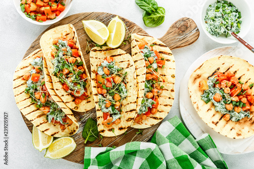 vegetarian snack of tacos with chickpea curry and sour cream sauce with parsley, spinach, green onions and sprouted flax seeds. healthy plant based food. top view on light background, flat lay