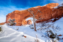 Tracks In The Snow Lead To A Famous Red Colored Arch In Utah In Winter