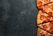 Cut Into Slices Delicious Fresh Pizza With Sausage Pepperoni And Cheese On A Dark Background. Top View With Copy Space For Text. Pizza On The Black Concrete Table. Flat Lay