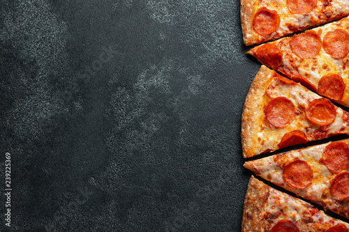 Cadres-photo bureau Pizzeria Cut into slices delicious fresh pizza with sausage pepperoni and cheese on a dark background. Top view with copy space for text. Pizza on the black concrete table. flat lay