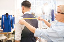 Side View Portrait Of Tailor Measuring Back Of Mature Bearded Man Fitting Bespoke Suit In Traditional Atelier Studio, Copy Space