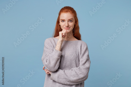 Fototapeta Beautiful playful red-haired girl standing holding hand near the chin looks conf
