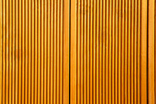 Yellow Wooden Wall Panels Decorated With Vertical Grooves. Abstract Geometrical Carved Wood Background