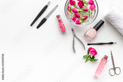 Fotografía manicure equipment with nail polish and rose petals white background top view sp