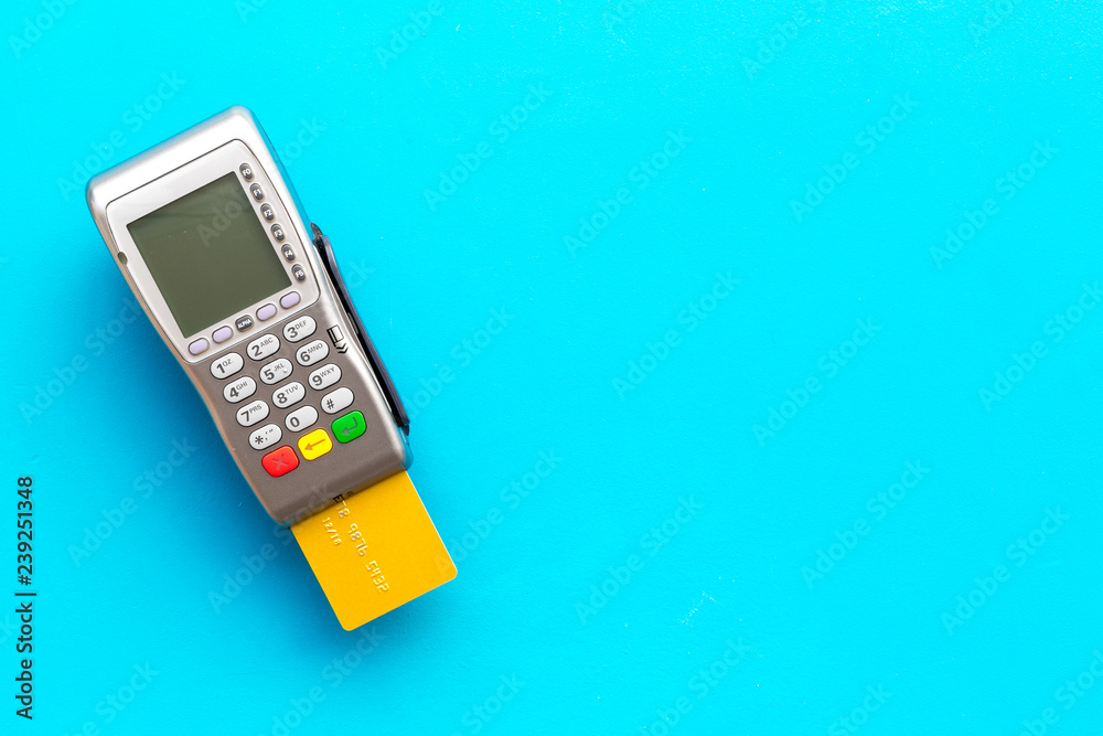 Fototapeta Pay by card. Bank card inserted in payment terminal on blue background top view copy space