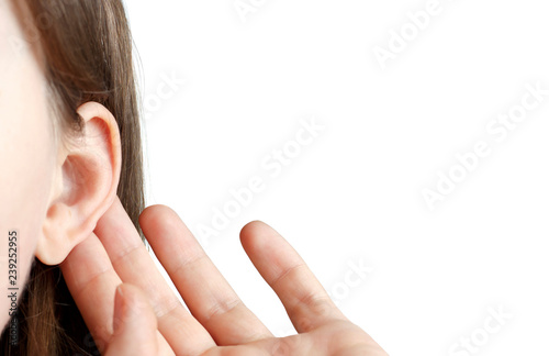Photo  The girl listens attentively with her palm to her ear, close-up isolated on whit