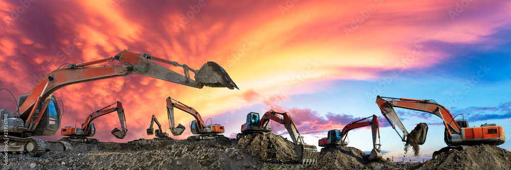 Fototapeta Many excavators work on construction site at sunset,panoramic view
