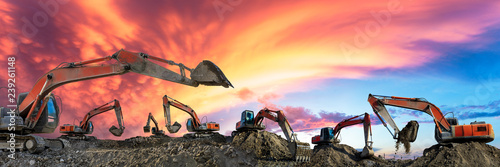 Obraz Many excavators work on construction site at sunset,panoramic view - fototapety do salonu