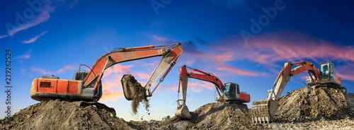 Pinturas sobre lienzo  Three excavators work on construction site at sunset,panoramic view