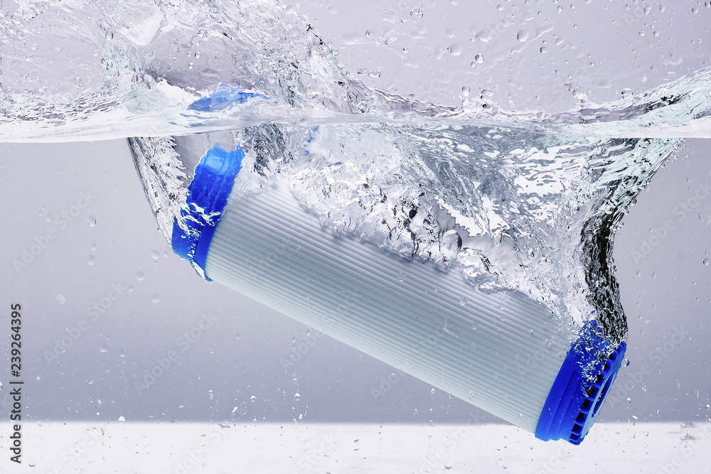 Fototapeta New carbon filter cartridge for house water filtration system isolated on white background. Splash. Concept.