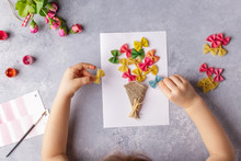 Paper Crafts For Mother Day, 8 March Or Birthday. Small Child Doing A Bouquet Of Flowers Out Of Colored Paper And Colored Pasta For Mom. Simple Gift Idea. View Top, Copy Space