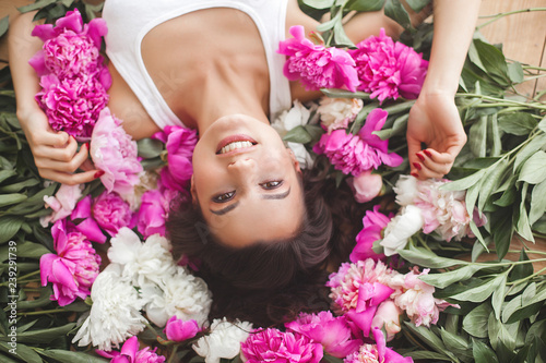 Young beautiful woman holding flowers. Attractive girl with peony pink. Beauty portrait. Female close up portrait