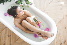 Young Beautiful Woman Taking Bath With Flowers And Milk. Attractive Girl Making Spa Procedure. Body Care. Female Taking Aroma Bath With Peony