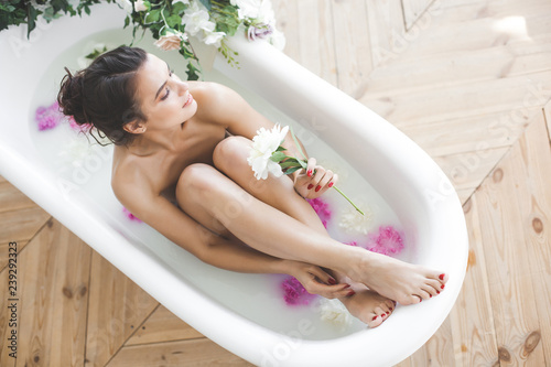 Fotografia Young beautiful woman taking bath with flowers and milk