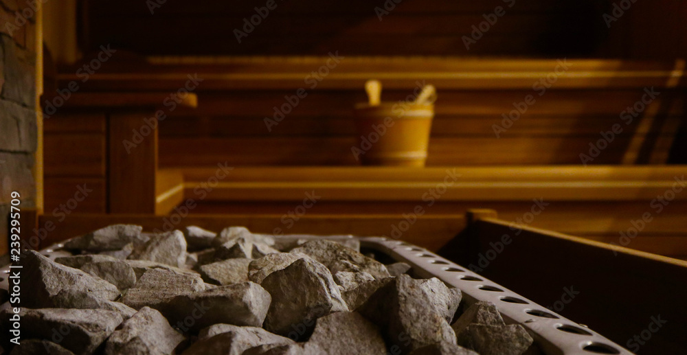 Fototapeta Wooden Bathhouse with a heating pot filled with stones, close up. Wooden sauna interior with equipment, coals, ladle, bucket.