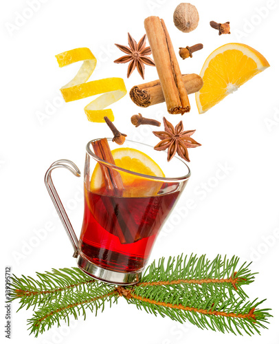 spices falling into a glass of mulled wine isolated on white