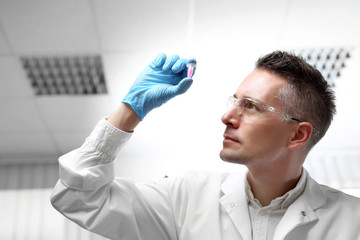 Badania i diagnostyka laboratoryjna.  Laborant ogląda preparat w próbówce.