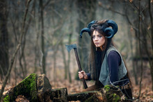 Beautiful Young Woman Warrior With Blue Eyes Wearing Ram Horns And Specific Makeup Holding Ax Hiding Behind Stumps In Forest, Stalking And Ready To Attack Or Defend Her Land.