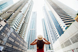 Back view of young woman in red summer dress holding with both hands straw hat looking up on skycrapers at downtown in modern city. Low angle view.