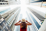Rear view of young woman in red dress holding with both hands straw hat amazed looking up on skycrapers at downtown in modern city. Low angle view.