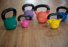Colorful Kettlebells In A Row On Wooden  Floor In A Gym, Green, Violet, Orange, Blue, Yellow, Pink