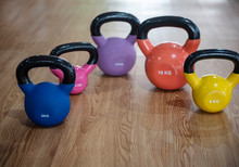 Colorful Kettlebells In A Row On Wooden  Floor In A Gym, Blue, Pink, Violet, Orange, Yellow,