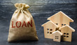 Wooden houses and a bag with the word Loan. Buying a home in debt. Family investment in real estate and risk management concept. Loan for a mortgage. apartment rental sale buy