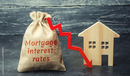 Obraz na plátně Bag with the money and the word Mortgage interest rates and arrow to down and house