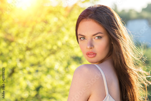 Closeup of girl posing outside in nature on a sunny day. Slika na platnu