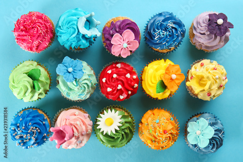 Delicious cupcakes on color background Wallpaper Mural