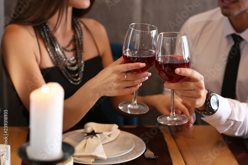 Loving couple with glasses of wine in restaurant on romantic date